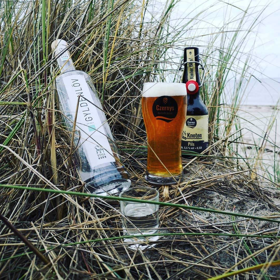 Bierglas, Bierflasche, Gyldenlövkorn und Kornglas in Dünen